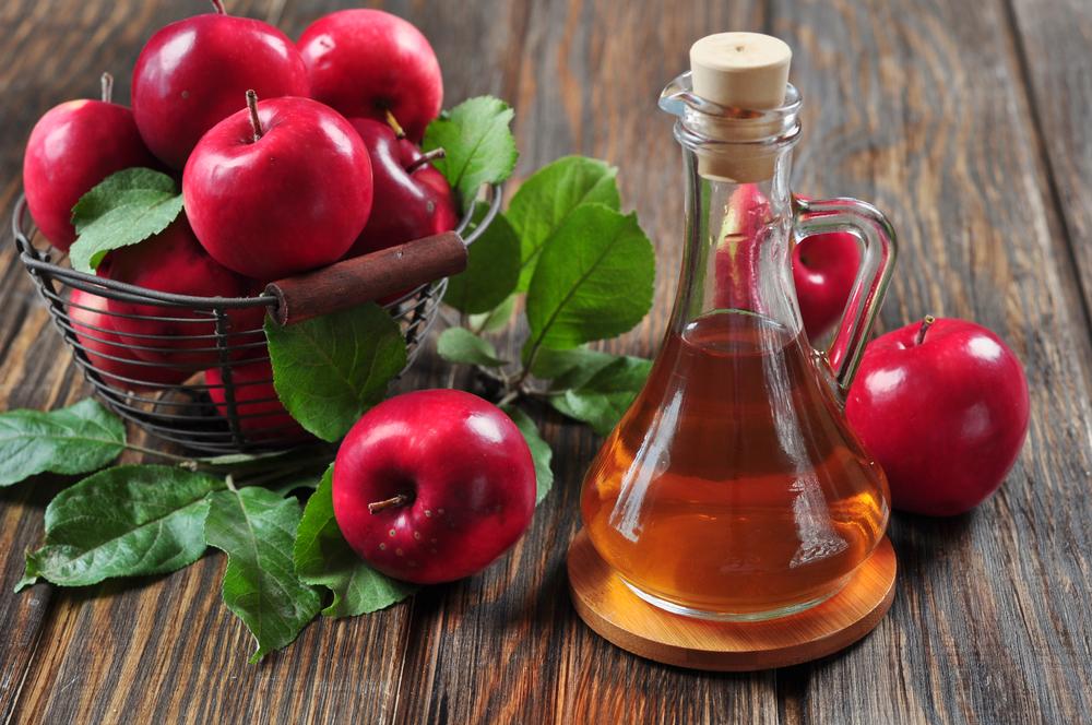 una ciotola di mele accanto a una boccetta di aceto di mele